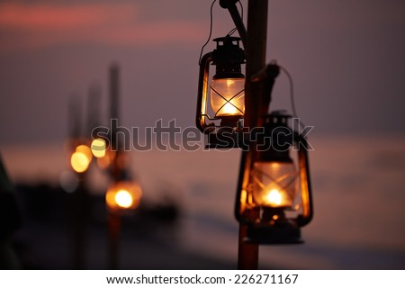 Old oil lanterns on the beach - stock photo