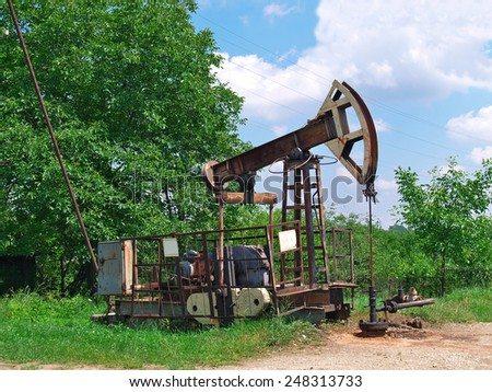 Old oil pupm jack on the oil well - stock photo
