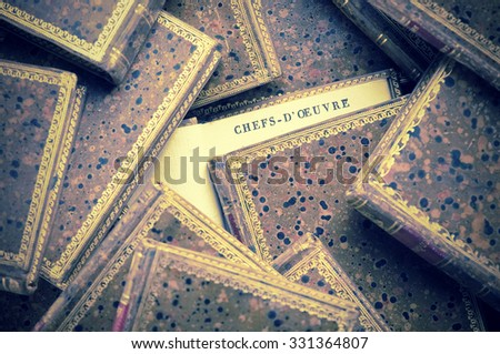 old open book among many coffee table books closed - stock photo