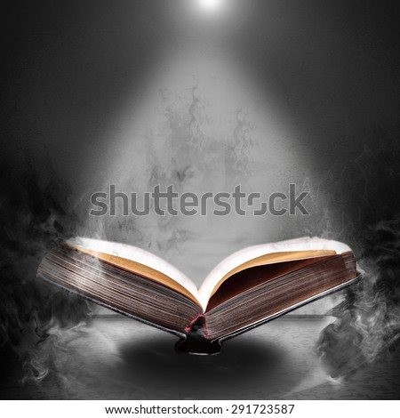 Old open book in the magical smoke on a gray concrete grunge background - stock photo