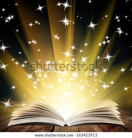 Old open book with magic light and falling stars on wood planks and dark abstract background - stock photo