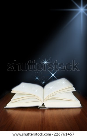 Old open book with magic light  on wood planks and dark abstract background - stock photo