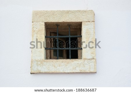 Old open window on white shabby wall with bars - stock photo