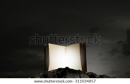 Old opened book with light coming from pages on dark background. - stock photo