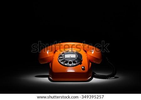 old orange retro phone on black background - stock photo