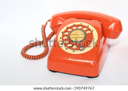 old orange telephone with rotary dial isolate on white - stock photo