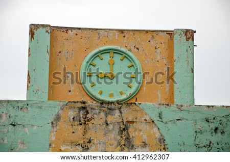 Old ornamental green and yellow clock, India - stock photo