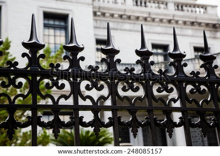Old ornamental wrought iron fence with spiked tops in front of stone building - stock photo