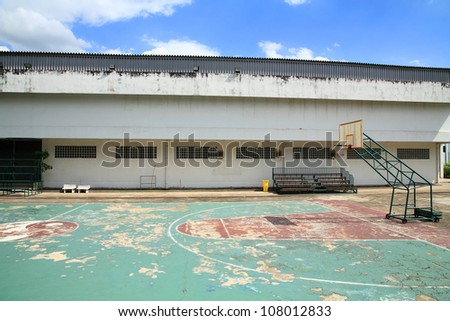 Old outdoor basketball court against blue sky - stock photo