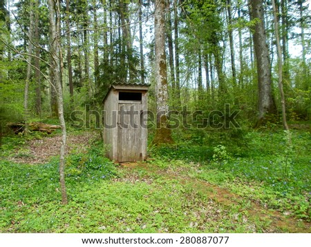 Old outdoor wooden toilet near the forest       - stock photo