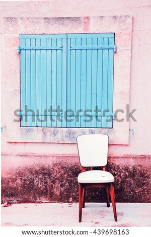 Old padded white leather chair standing near the window with closed wooden shutters outside of  the old house with stucco wall. Provence, France. Toned photo. - stock photo
