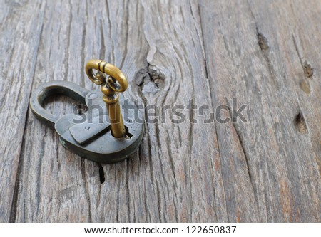 Old padlock and key on a wooden table background - stock photo