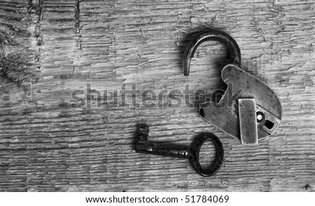 Old padlock and key on wooden background (black and white) - stock photo