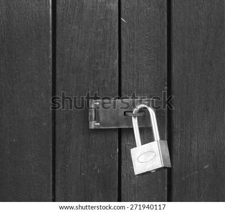 Old padlock on a wooden door - stock photo