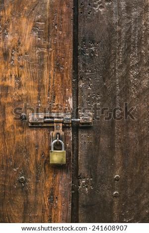 Old padlock on a wooden door,old wooden door - stock photo
