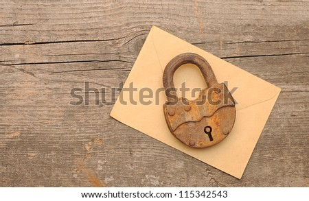 Old padlock on yellow envelope over  wooden background. With copy space - stock photo
