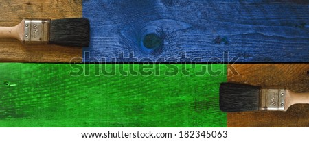 Old paintbrushes staining a piece of timber - stock photo