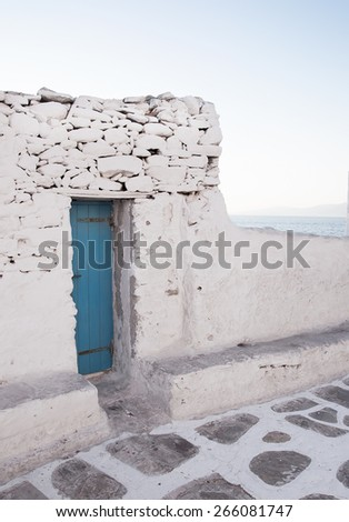 Old painted blue door on the whitewashed wall. Background. Typical for Greece. - stock photo
