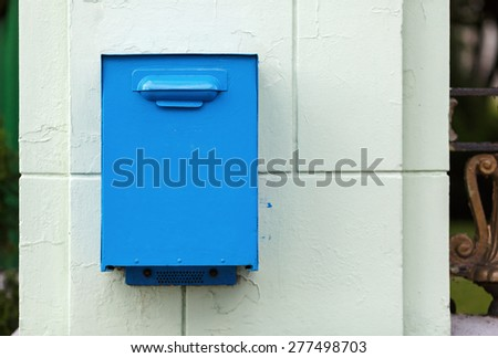 Old, painted in blue mailbox in retro style. - stock photo