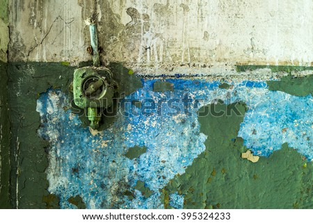 Old painted plastic rotary light switch on a grunge green peeling concrete wall background - stock photo