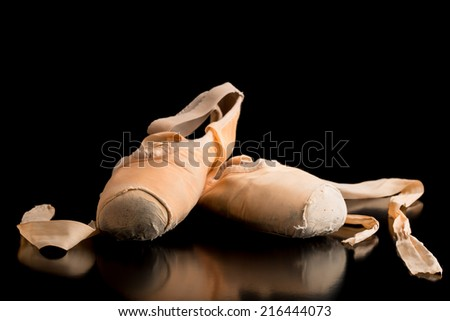 Old pair of neatly arranged ballet shoes on a dark background with copyspace and reflection. - stock photo