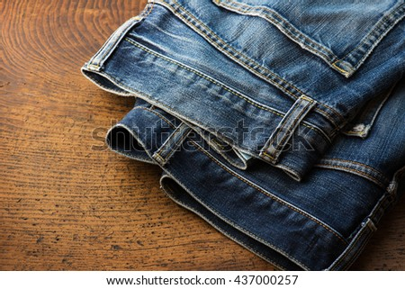 Old pair of nicely faded blue jeans on rustic table.  - stock photo