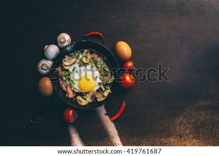 old pan. fried egg, bacon, mushrooms, green onion - tasty Breakfast or snack. On a dark wooden table. Top view with copy space - stock photo