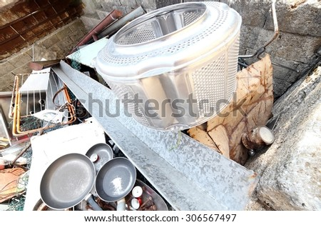 old pans and washing machine basket and rusty iron ore dump in special waste landfill - stock photo