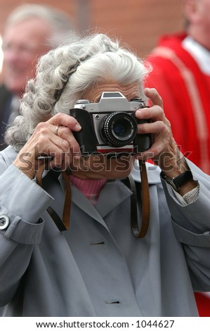 Old Paparazzi: an old woman taking photos with a retro camera. - stock photo