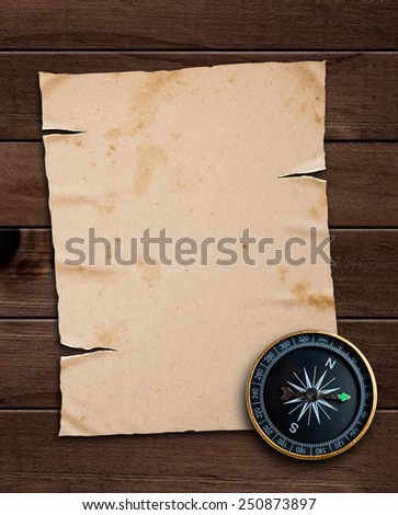 old paper and compass on a wooden table - stock photo