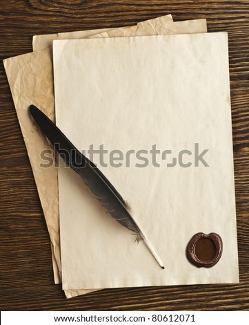 old paper and feather with a wax seal on a wooden background - stock photo