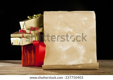 old paper, feather and gifts on a black background - stock photo