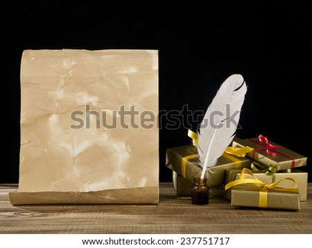 old paper, gifts and feather on a black background - stock photo