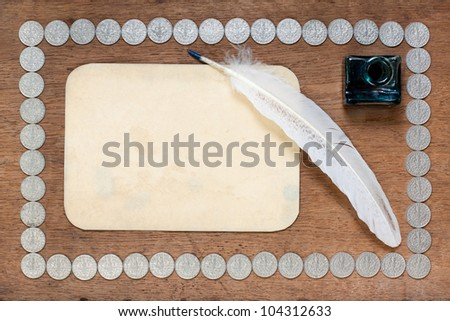 Old paper, quill and inkwell on wood with coins - stock photo