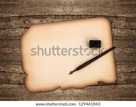 old paper sheet and antique ink pen over rustic wooden background. grunge vintage backdrop - stock photo