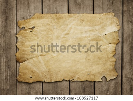 Old paper sheet at grunge wooden background with copy space - stock photo