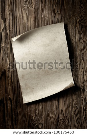 old paper sheet on aged wooden wall - stock photo