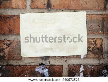 Old paper sheet stick on brick wall - stock photo