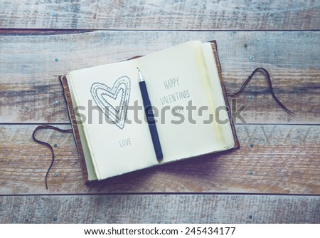 Old paper sketch book with hand-drown doodle heart. Happy Valentines Day! - stock photo