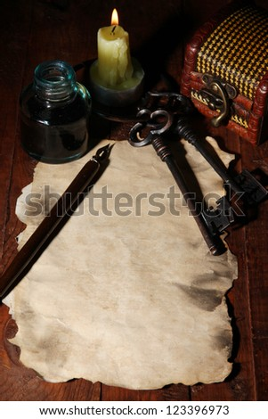 Old paper with ink pen near lighting candle on wooden table - stock photo