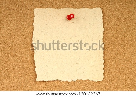 Old paper with pin on wooden background - stock photo