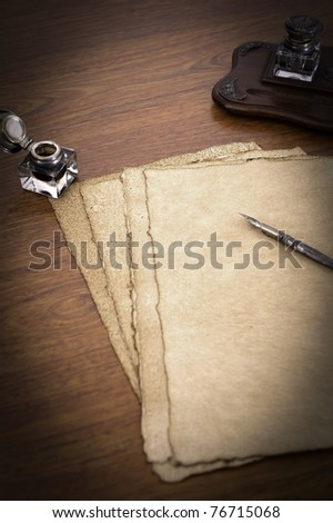 Old papers on a desk with ink and pen - stock photo