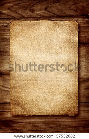 Old parchment on wooden background - stock photo