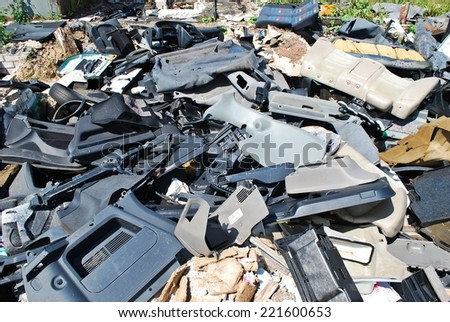 Old parts scrapped cars in a junk yard. Plastic parts. - stock photo
