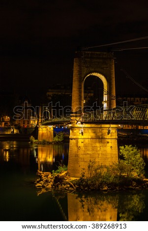 Old Passerelle du College bridge over Rhone river in Lyon, France at night - stock photo