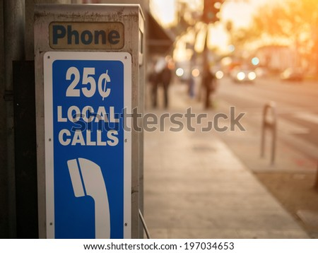 Old pay phone detail with city street in the background - stock photo