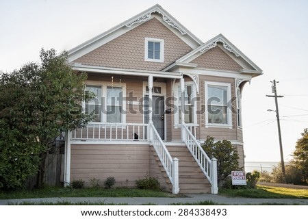 Old peach colored Victorian house for rent - stock photo