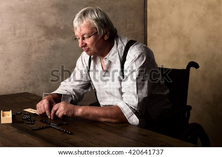 Old pensioner in nursing home playing domino alone - stock photo