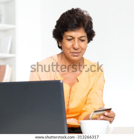 Old people and modern technology concept. Portrait of a 50s Indian mature woman hand holding credit card, using online internet payment at home. Indoor senior people living lifestyle. - stock photo