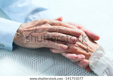 Old people holding hands. Closeup. - stock photo